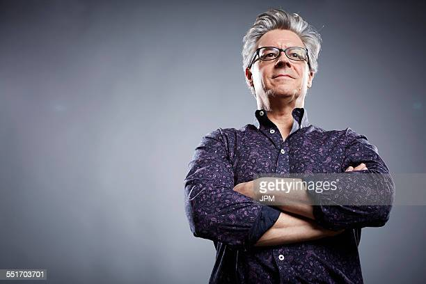 low angle studio portrait of mature businessman with arms folded - orgoglio foto e immagini stock