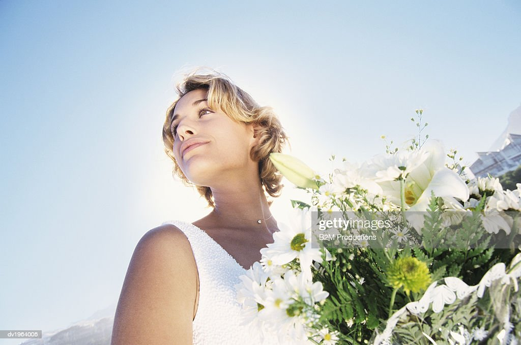 Low Angle Tilted Shot of a Serene Bride Holding a Bouquet of White Flowers : Stock Photo
