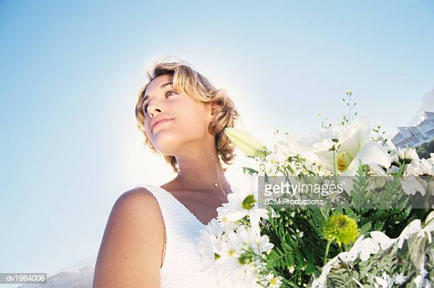 Low Angle Tilted Shot of a Serene Bride Holding a Bouquet of White Flowers