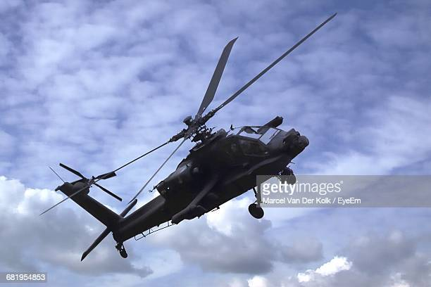 Low Angle View Apache Helicopter Flying In Cloudy Sky