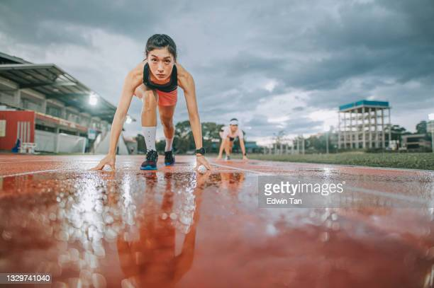 low angle view asian chinese female athletes lining up  starting line aerodynamic shape getting ready to run at track rainy late evening in stadium with cloudy weather - forward athlete stock pictures, royalty-free photos & images