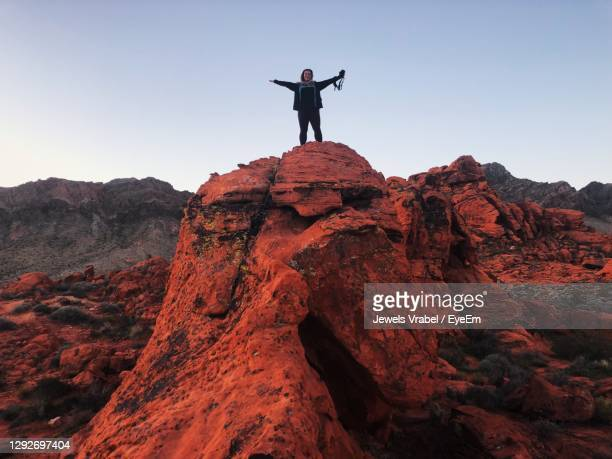 low angle view at sunrise of womman standing on rock holding camera - las vegas stock pictures, royalty-free photos & images