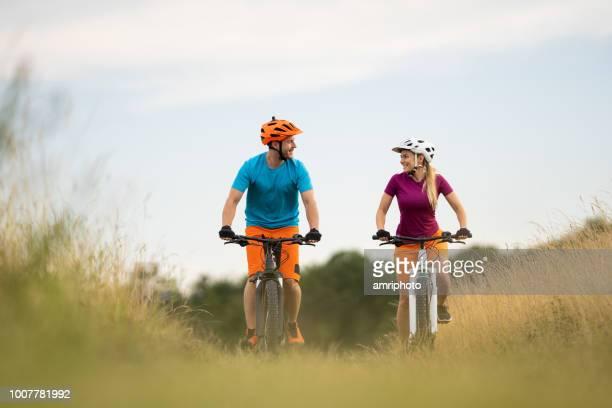 niedrigen winkel ansicht glückliche paar radfahren in grünland lächeln einander an - erforschung stock-fotos und bilder