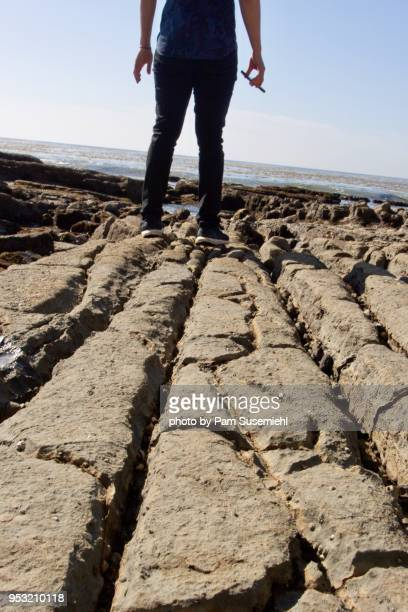 low angle view, man on coastal rock formation - inclinando se - fotografias e filmes do acervo