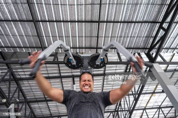 low angle view muscular bodybuilder asian man doing chest workout on exercise machine in gym - skinhead stock pictures, royalty-free photos & images