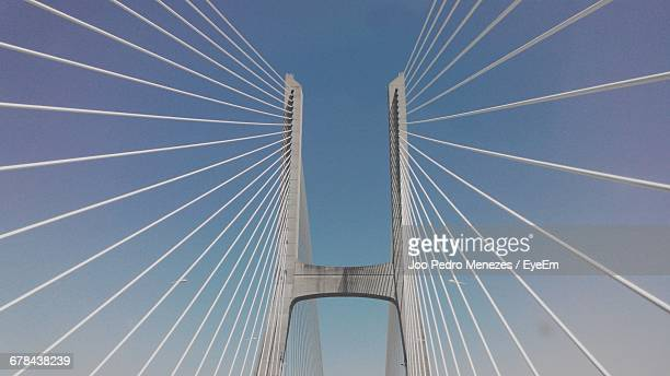 low angle view of 25 de abril bridge against sky - suspension bridge stock pictures, royalty-free photos & images