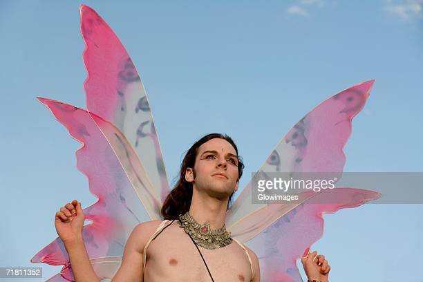 Low angle view of a bare chested gay man in a fairy costume
