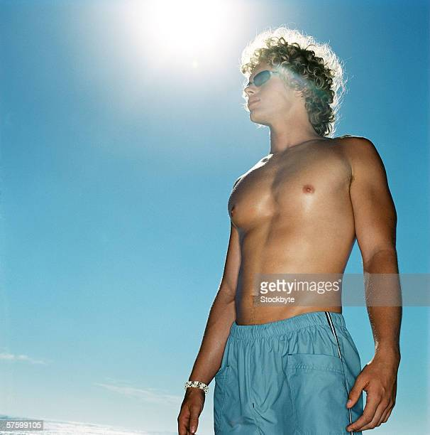 low angle view of a bare chested man standing under the sun - bare chested man foto e immagini stock