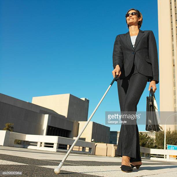 low angle view of a blind businesswoman walking with the aid of a white stick