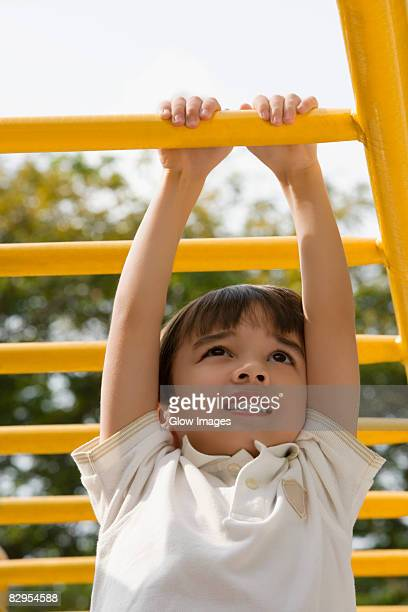 Low angle view of a boy hanging on monkey bars