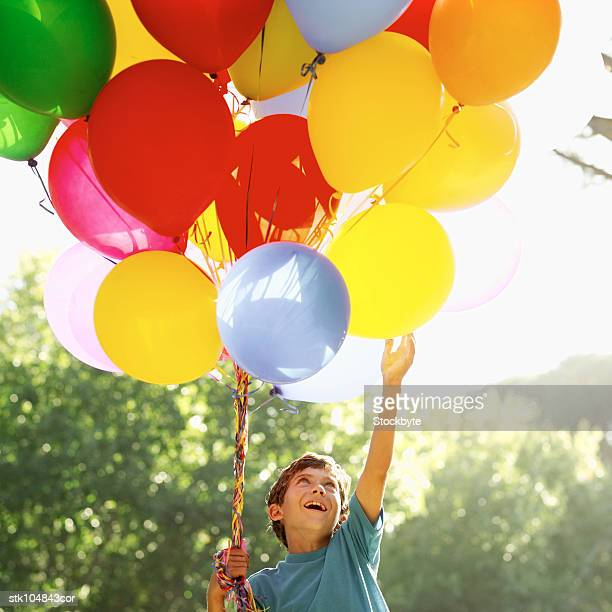 low angle view of a boy holding balloons
