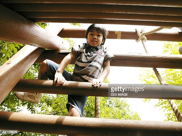 Low angle view of a boy playing on a jungle gym