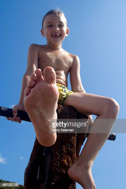 Low angle view of a boy sitting on the fence, Anapa, Krasnodar Krai, Russia