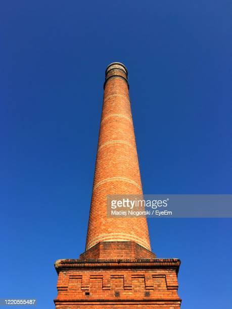 low angle view of a brick chimney against blue sky - 煙突 ストックフォトと画像