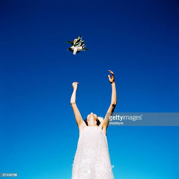 low angle view of a bride jumping to throw the bouquet