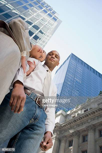Low angle view of a businessman and a businesswoman standing with arm in arm