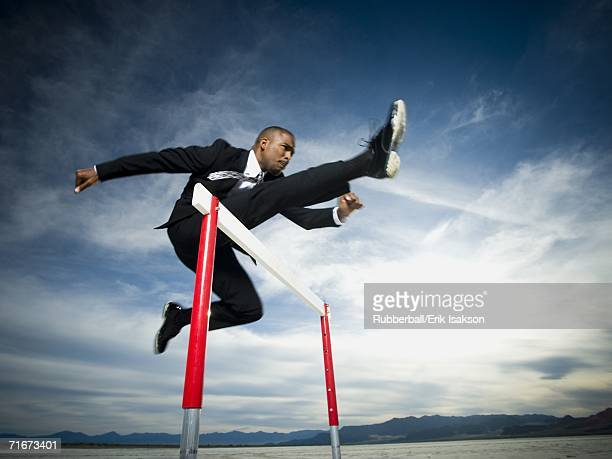 low angle view of a businessman jumping over a hurdle in a race - hurdling track event stock pictures, royalty-free photos & images