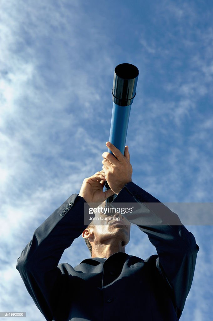 Low Angle View of a Businessman Looking Through a Telescope : Stock Photo
