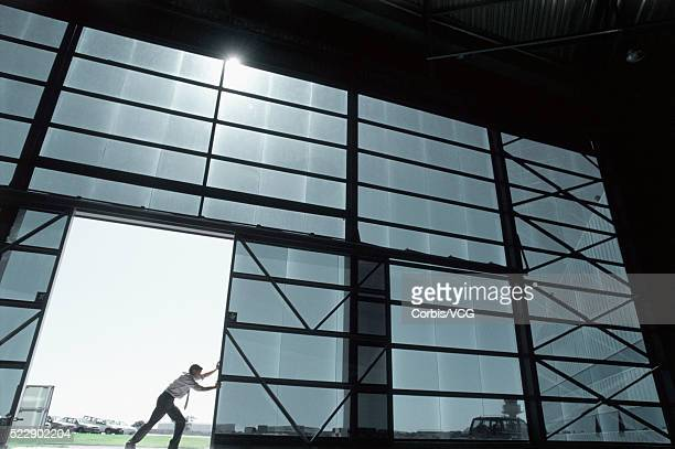 Low angle view of a businessman pushing a large sliding door