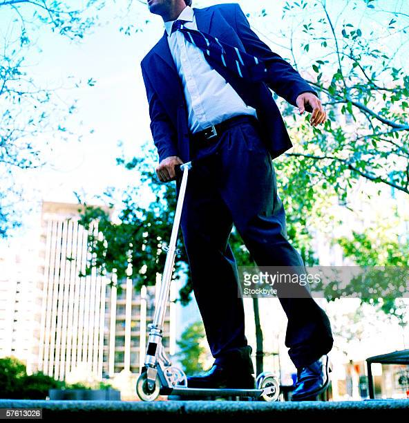 Low angle view of a businessman riding a scooter on the street