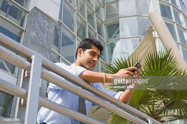 Low angle view of a businessman text messaging on a mobile phone, Gurgaon, Haryana, India
