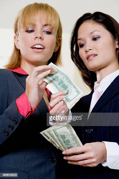 Low angle view of a businesswoman giving a dollar bill to another businesswoman