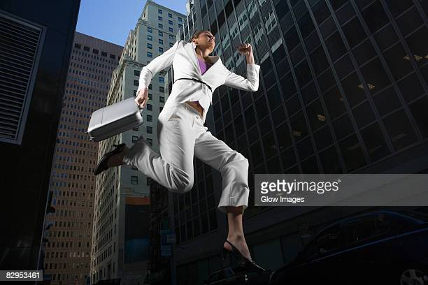 Low angle view of a businesswoman jumping with a briefcase