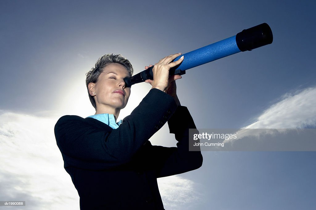 Low Angle View of a Businesswoman Looking Through a Telescope : Stock Photo