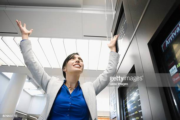 Low angle view of a businesswoman smiling with her arms raised at an airport