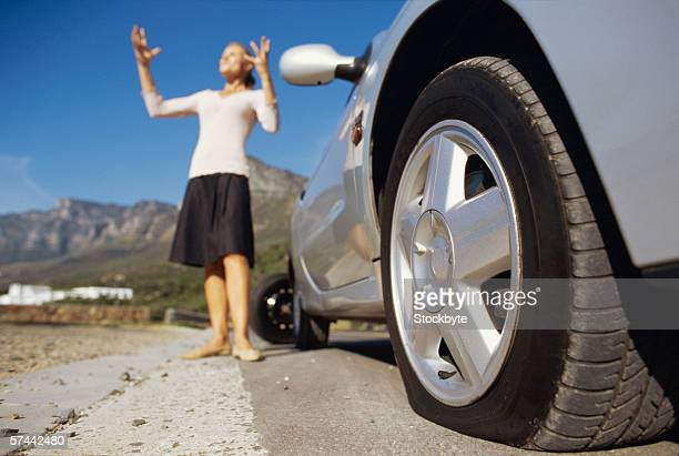low angle view  of a car with a flat tyre and a woman - flat tire stock pictures, royalty-free photos & images