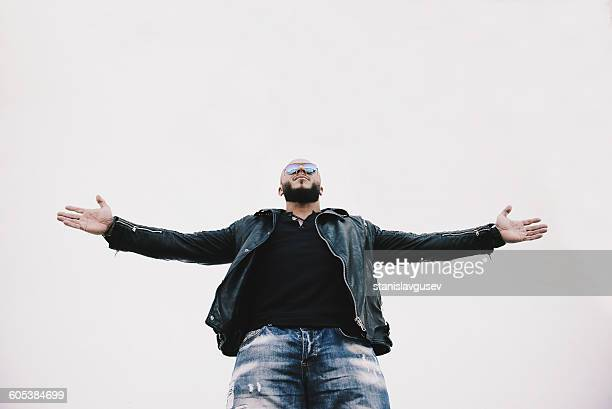 Low angle view of a cool man with arms outstretched