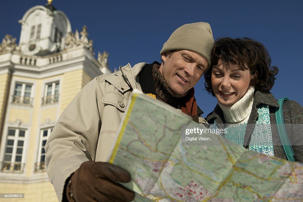 Low Angle View of a Couple Reading a Map : Stock Photo