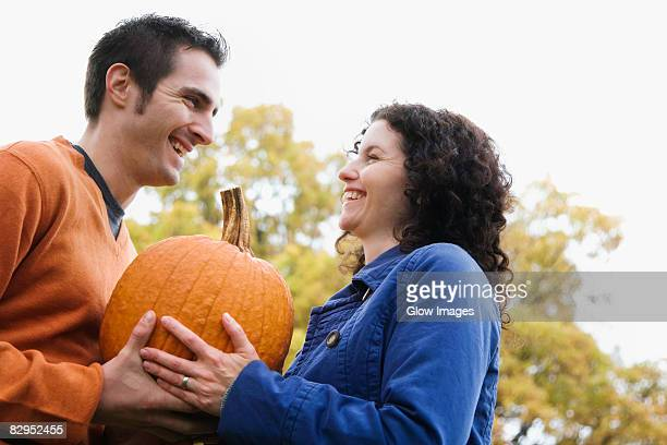 low angle view of a couple sharing a pumpkin and smiling - schwarzes haar stock-fotos und bilder