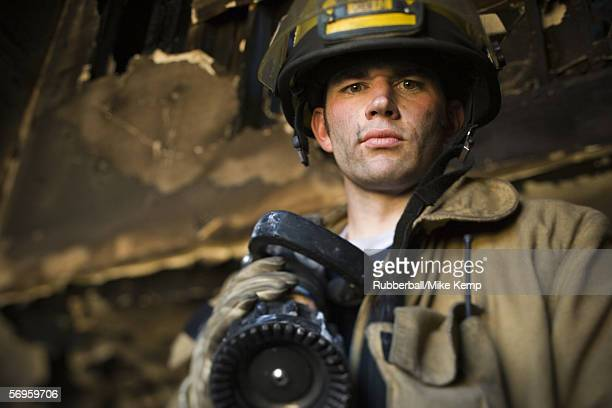 low angle view of a firefighter holding a fire hose - fire protection suit stock photos and pictures