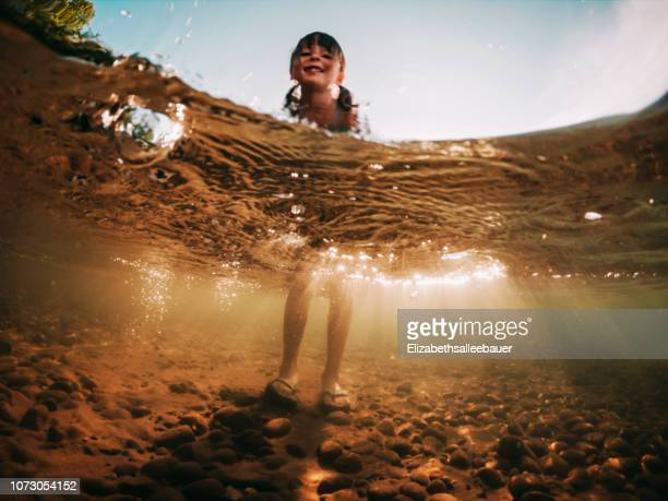 low angle view of a girl standing in a lake, lake superior, united states - wading stock pictures, royalty-free photos & images
