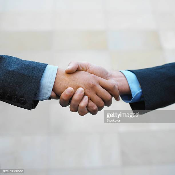 low angle view of a handshake between a businessman and businesswoman - number of people stock photos and pictures