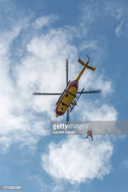low angle view of a helicopter rescue against a cloudy clear blue sky - laurent sauvel photos et images de collection