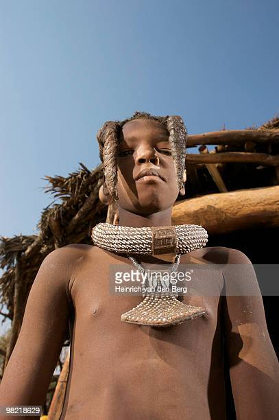 Low angle view of a Himba teeanage boy looking at camera, Epupa Falls area, Kaokoland, Namibia