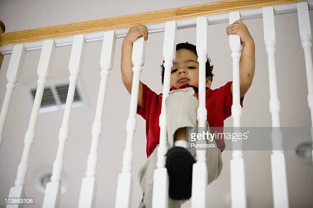 low angle view of a little boy standing behind stair rails - child behind bars stock pictures, royalty-free photos & images