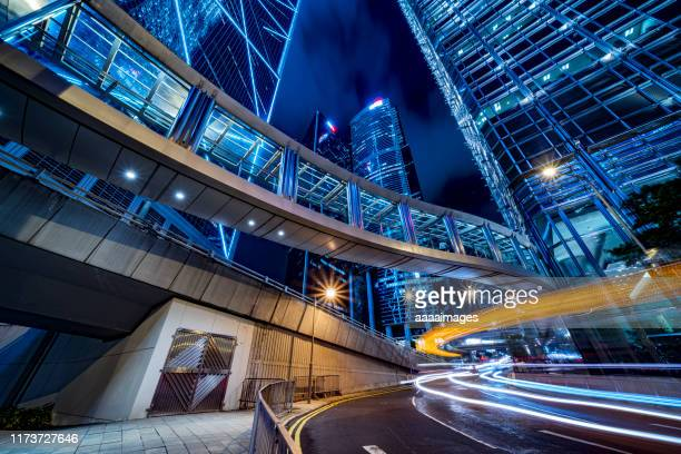low angle view of a long covered footbridge links up modern office buildings - elevated walkway stock pictures, royalty-free photos & images