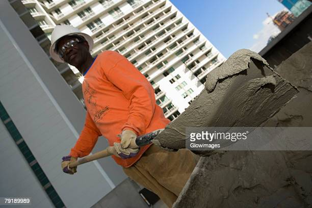 Low angle view of a male construction worker shoveling cement