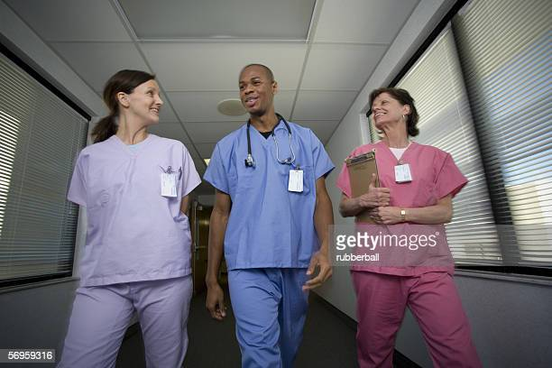 Low angle view of a male doctor and two female doctors walking in a corridor