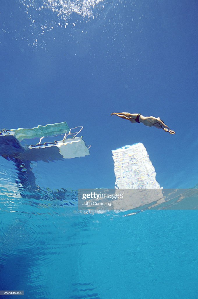 Low Angle View of a Man Diving From a Diving Board : Stockfoto