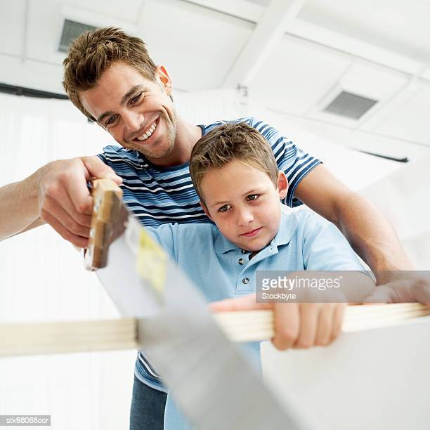 low angle view of a man helping his son saw a piece of wood