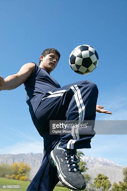 Low Angle View of a Man Playing Keepy Uppy