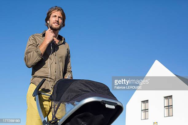 Low angle view of a man standing with a baby stroller