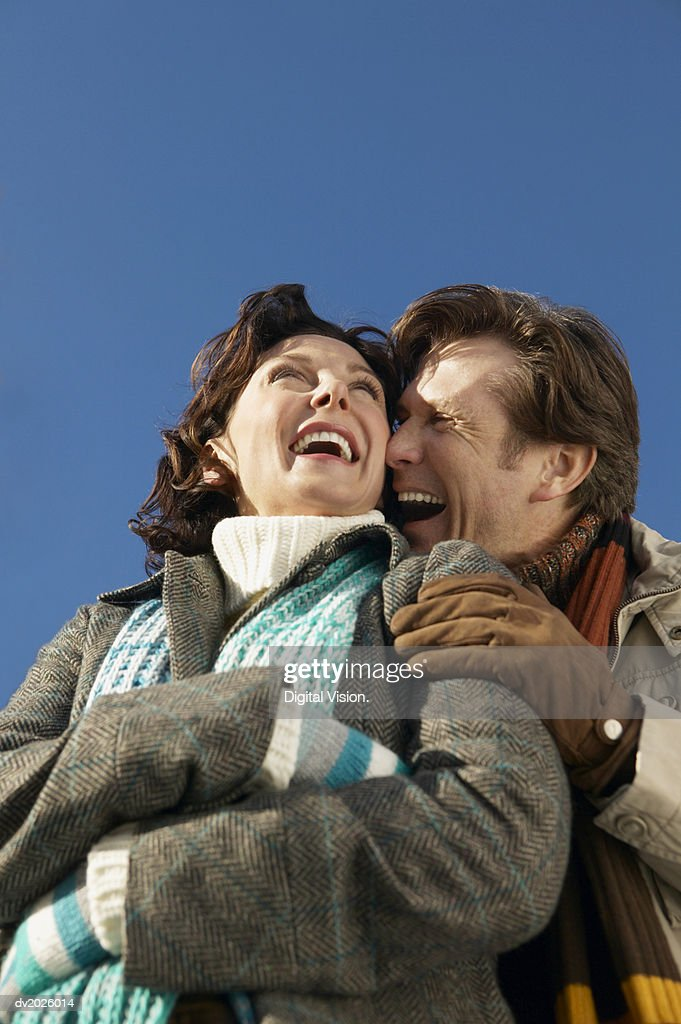Low Angle View of a Mature Couple in Winter Clothing Embracing and Laughing : Stock Photo