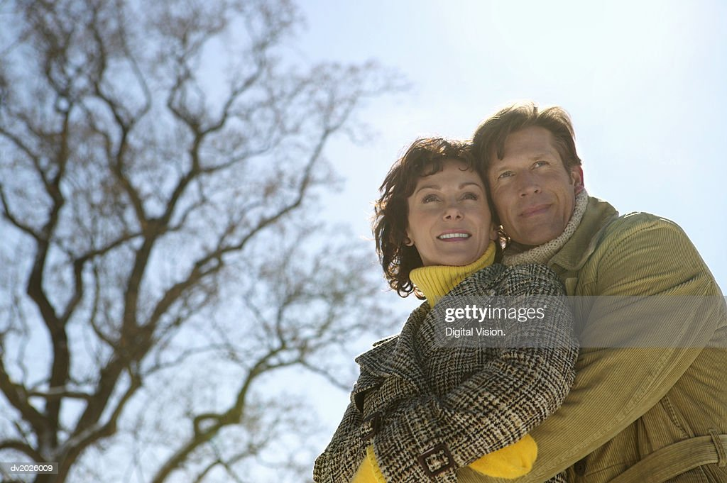 Low Angle View of a Mature Couple in Winter Coats Standing Outdoors Embracing : Stock Photo