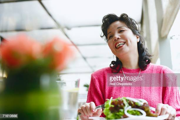 Low angle view of a mature woman seated at the table in a restaurant smiling