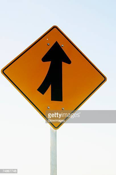 Low angle view of a merging sign